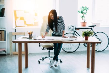 persona de pie: Longitud total de joven y bella mujer asiática que hace algunas notas en planos mientras se inclina a la mesa en la oficina Foto de archivo