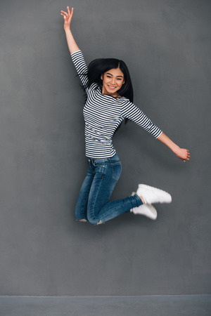 asian lady: Beautiful young cheerful Asian woman looking at camera with smile while jumping against grey background