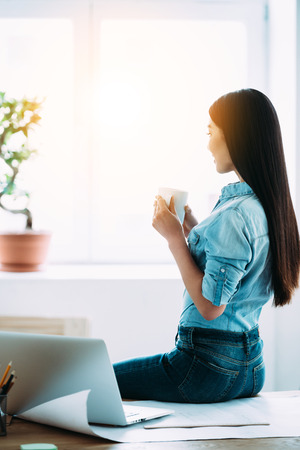 asian lady: Rear view of young Asian woman holding coffee cup and looking through window while sitting on table at her working place