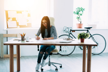 japanese ethnicity: Full length of young beautiful Asian woman drafting at blueprints while sitting at her working place