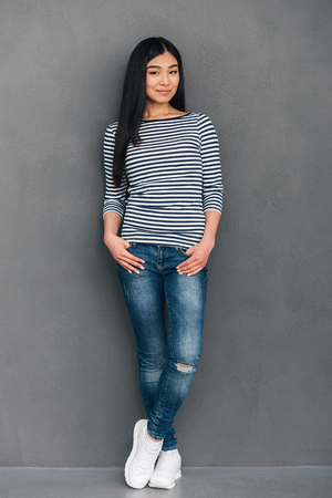 japanese ethnicity: Beautiful lady. Full length of beautiful young Asian woman keeping hands in pockets and looking at camera with smile while standing against grey background