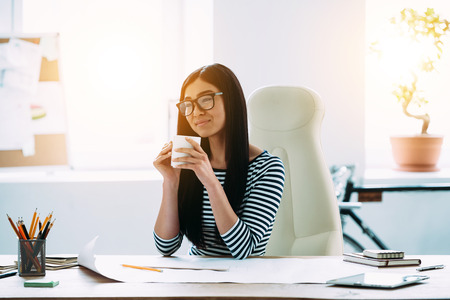 thinking woman: Beautiful young Asian woman in glasses holding coffee cup and looking away with smile while sitting over blueprints at her working place