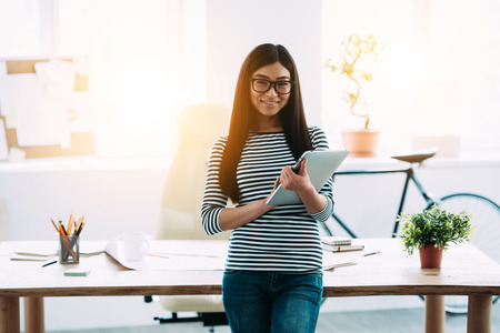 Krásná mladá asijské žena v brýlích drží digitální tablet a při pohledu na kameru s úsměvem, když stál před ní pracovní místa Reklamní fotografie