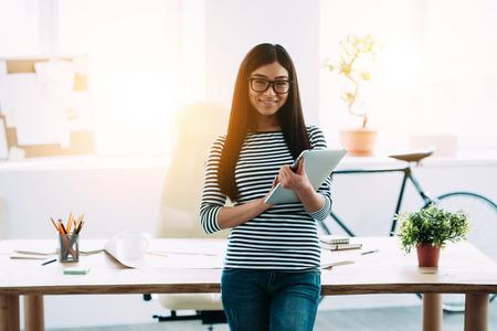 La mujer asiática joven hermosa en los vidrios que sostienen la tableta digital y mirando a cámara con una sonrisa mientras se está frente a su lugar de trabajo