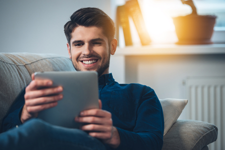 only one person: Close-up of handsome young man using his digital tablet with smile while lying down on the couch at home Stock Photo