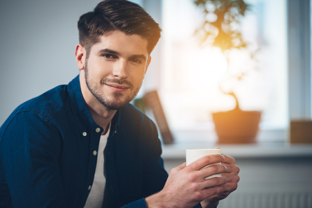 bel homme: Close-up partie du beau jeune homme tenant la tasse de caf� avec le sourire et en regardant la cam�ra assis sur le canap� � la maison Banque d'images