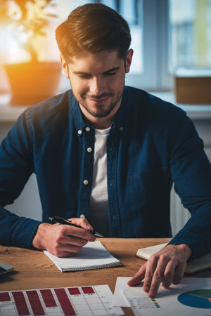 note pad: Cheerful young handsome man working with charts with smile while sitting at his working place Stock Photo