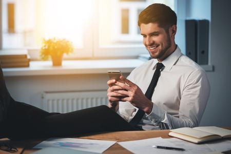ハンサムな若い男笑顔で彼のスマート フォンを使用して、彼の職場に座ってテーブルに足を維持します。