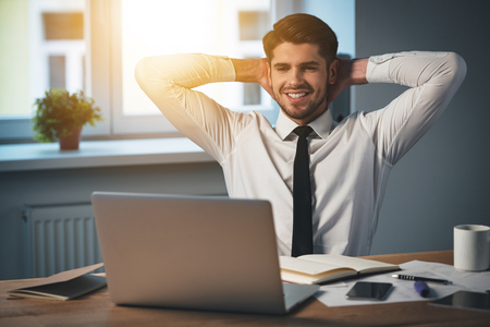 only one person: Handsome young cheerful man keeping hands behind head and smiling while sitting at his working place Stock Photo