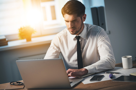 working on computer: Top view of pensive young handsome man using his laptop while sitting at his working place Stock Photo