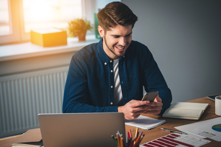 working place: Cheerful young handsome man using his smartphone with smile while sitting at his working place