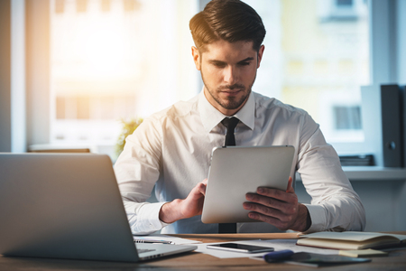 pensive man: Pensive young handsome man using his digital tablet while sitting at his working place Stock Photo