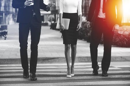 personas en la calle: Caminando hacia el éxito juntos. Imagen recortada de tres hombres de negocios que cruza la calle Foto de archivo