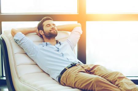 Hora de relaxar. Handsome jovem segurando as mãos atrás da cabeça enquanto dorme no sofá Imagens