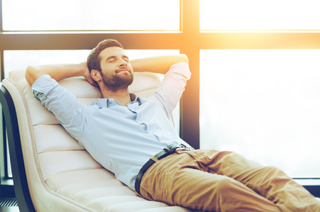 domestic: Time to relax. Handsome young man holding hands behind head while sleeping on the couch Stock Photo