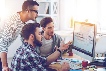 Diskusi o nový projekt. Tři mladí podnikatelé diskutují něco, co při pohledu na monitor počítače spolu