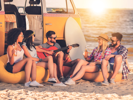 Carefree fun. Group of joyful young people drinking beer and playing guitar while sitting on the beach near their retro minivan Stock Photo