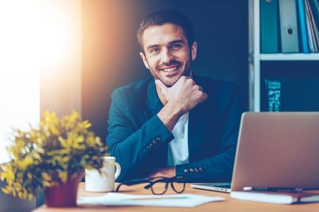 Sebevědomý a pohledný. Jistý mladý muž, který držel ruku na bradě a úsměvem, zatímco sedí u svého pracovního místa v kanceláři