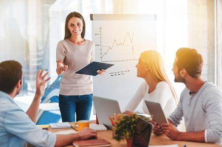 Discutir novas idéias de negócios. Jovem alegre em pé perto de quadro branco e sorrindo enquanto seus colegas sentado à mesa