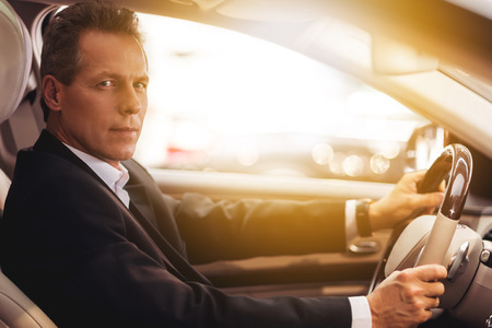 Confident driver. Side view of confident senior man in formalwear sitting in car and looking at camera Stock Photo