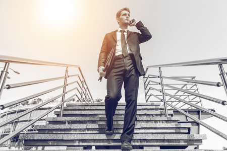 moving down: Confident businessman. Black and white image of confident young man in formalwear talking on the mobile phone while moving down by staircase
