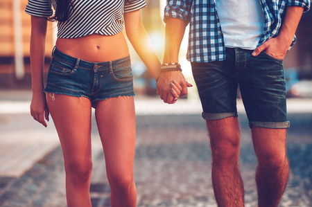 holding hands while walking: Always together. Close-up of beautiful young loving couple holding hands while walking along the street