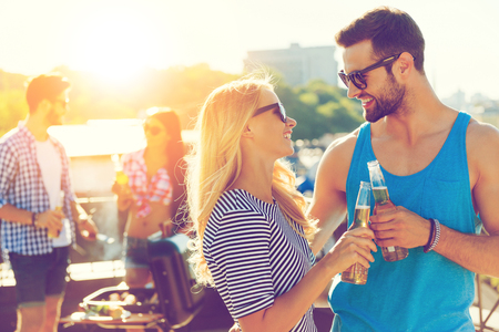 barbecuing: Cheers! Smiling young couple clinking glasses with beer and looking at each other while two people barbecuing in the background