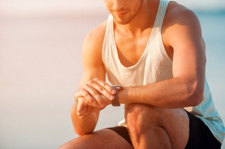 checking time: Checking time. Cropped image of young muscular man checking time on his watches while sitting outdoors