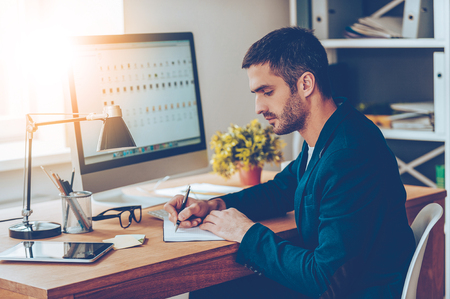 Working moments. Side view of confident young man writing something in his notebook while sitting at his working place in office photo