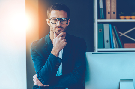 Confident business expert. Confident young man in smart casual wear holding hand on chin and looking at camera while leaning at computer monitor in office