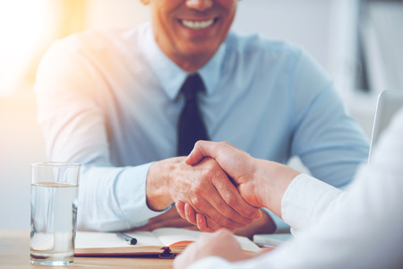 Bom negócio. Close-up de dois executivos apertando as mãos ao sentar-se no local de trabalho