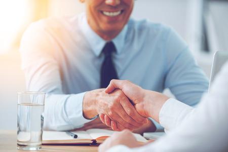 persona sentada: Buen negocio. Primer plano de dos personas de negocios apret�n de manos mientras est� sentado en el lugar de trabajo Foto de archivo