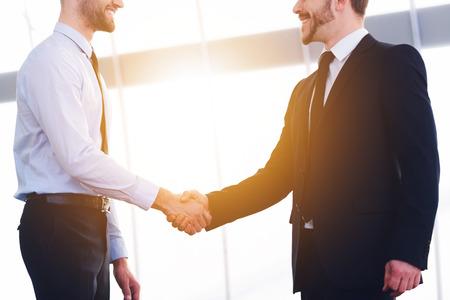 buen trato: Sellado de buen trato. Dos hombres de negocios alegre dando la mano y sonriendo mientras está de pie en el interior