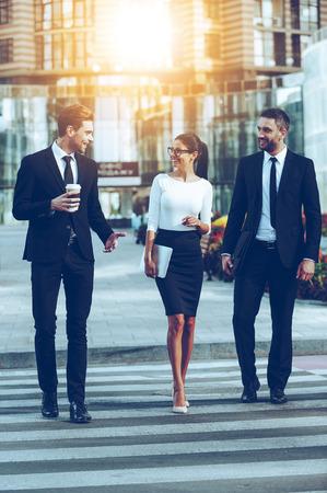 Auf dem Weg zur Arbeit. In voller Länge von drei lächelnde Geschäftsleute, miteinander zu reden, während die Straße überqueren