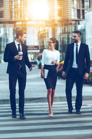 three persons: On the way to work. Full length of three smiling business people talking to each other while crossing the street