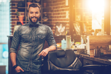 Welcome to my barbershop! Cheerful young bearded man looking at camera and holding hand in pocket while leaning on chair at barbershop Stock Photo