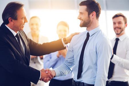 Bom trabalho! Dois homens de negócios alegres que agitam as mãos enquanto seus colegas aplaudindo e sorrindo no fundo