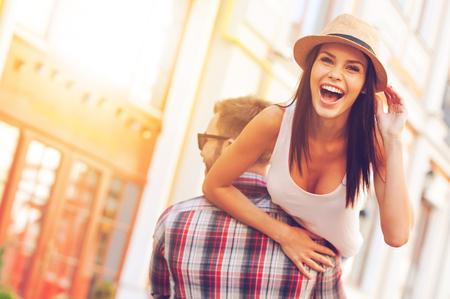 Genieten van prachtige dag. Achter mening van jonge vrolijke man met zijn mooie vriendin op schouder tijdens het wandelen door de straat