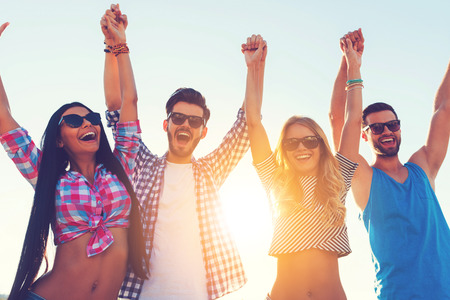 four people: Enjoying carefree time together. Low angle view of four cheerful young people holding hands and keeping arms raised while standing against sky