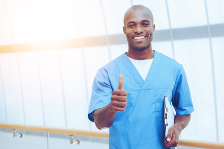 Good news! Happy young African doctor in blue uniform holding clipboard and showing his thumb up