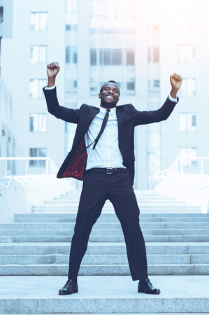man at work: Celebrating success. Full length of happy young African man in formalwear keeping arms raised and expressing positivity while standing outdoors Stock Photo