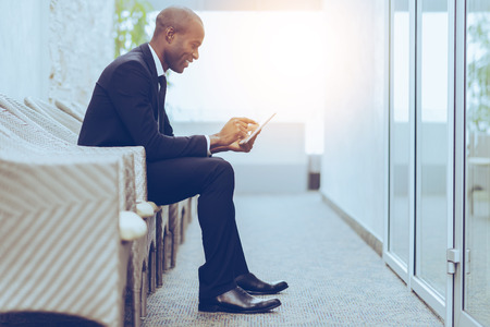 adults only: Checking his business schedule. Side view of cheerful young African businessman working on digital tablet while sitting on the chair