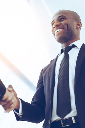 black hands: Sealing a deal. Close-up of low angle view of business men shaking hands Stock Photo