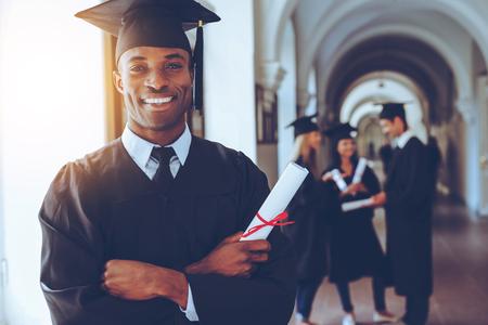 Glücklicher Absolvent. Happy African Mann in Graduierung Kleider Holdin
