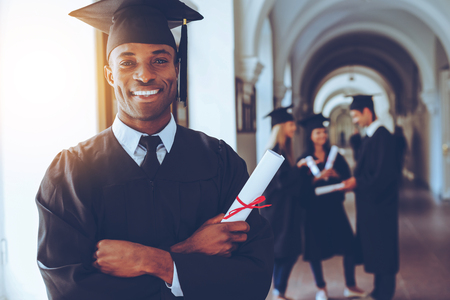 standing out in the crowd: Happy graduate. Happy African man in graduation gowns holdin Stock Photo
