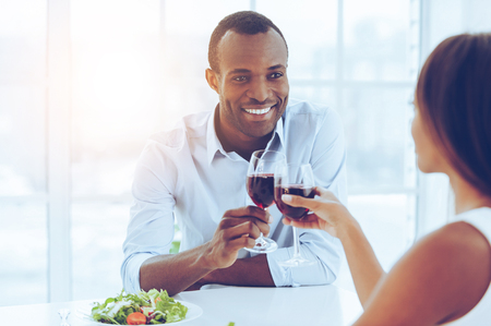 two men: Romantic dinner.. Beautiful young African couple sitting together at the table and holding wineglasses