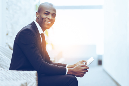 Confident businessman. Side view of cheerful young African businessman working on digital tablet and smiling at camera Stock Photo