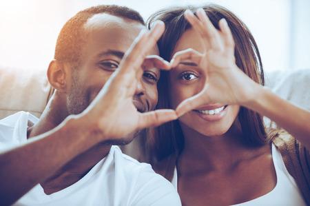 ¡El amor está en el aire! pareja africana joven hermosa que se sienta cerca uno del otro y mirando a través de una forma de corazón con sus dedos Foto de archivo