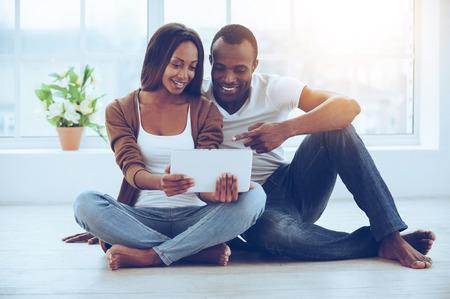position d amour: Examiner leur nouvel onglet. Belle jeune couple africain utilisant tablette numérique tout en étant assis ensemble sur le plancher à leurs appartements