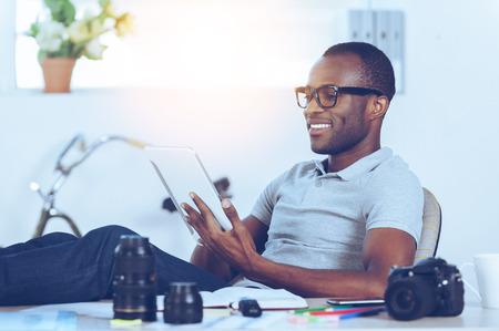 Těší jeho pracovní den. Pohledný mladý africký muž v oblečení pro volný čas sedí u svého pracovního místa a pracuje na digitální tablet